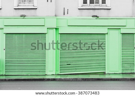 Closed shutters on the front of a shop in the UK - stock photo