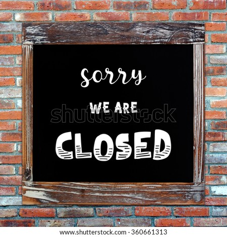 Closed sign on vintage chalk board over brick wall background - stock photo