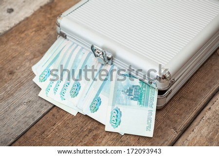 Closed steel case with Russian banknotes inside on wooden floor - stock photo