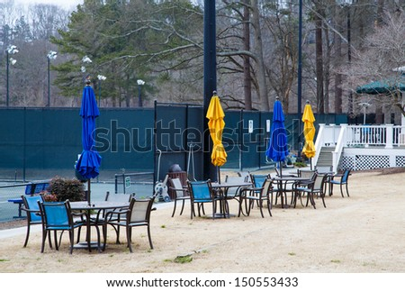 Closed tennis courts in winter with blue and yellow sun umbrellas - stock photo