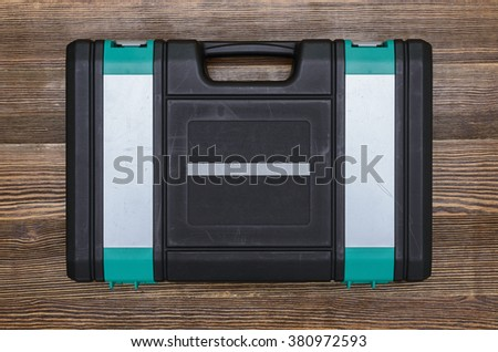 Closed toolbox with different instruments on wooden workbench - stock photo