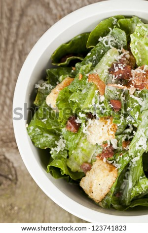 Closed up cropped bowl of caesar salad placed on top of a wooden table - stock photo