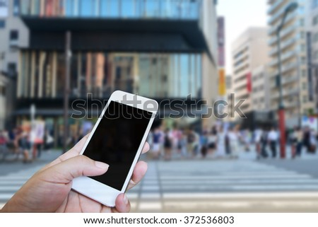 Closed up hand of man touch screen, City view background - stock photo