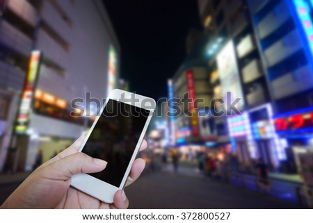 Closed up hand of man touch screen. Shopping street background - stock photo