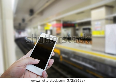 Closed up hand of man touch screen. Train station background - stock photo