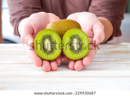 Closed up of fresh and sweet kiwi fruits on hands for a light tasty meal - stock photo