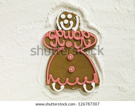 Closed up shot of a gingerbread woman lying on flour - stock photo