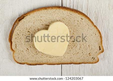 Closed up shot of a piece of bread with heart shaped butter - stock photo
