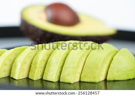 Closed up Slice avocado fruit on black dish - stock photo