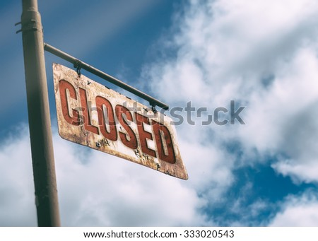 Closed Vintage Rusted Sign. Old rusted sign hanging off the side of an old country road. Closed sign. - stock photo