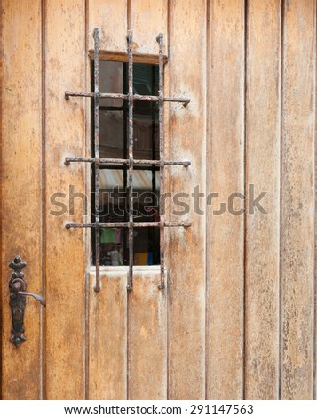 Closed weathered rustic door with barred window - stock photo