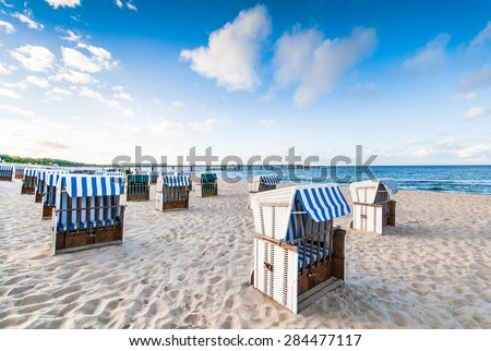 Closed wicker beach chairs on empty sandy beach at Baltic Sea, calm before rush - stock photo