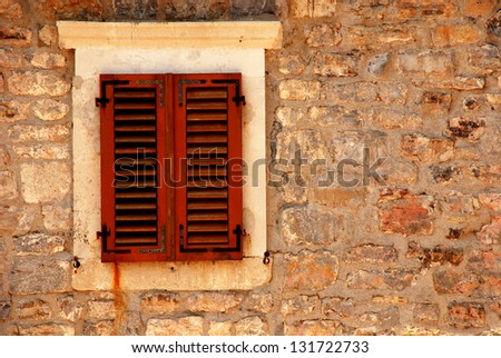 Closed window with shutters in old rough stone wall of ancient italian house. image with copy space - stock photo