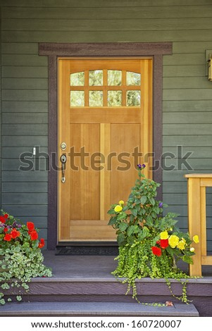 Closed wooden door of a home with green siding and flowerpots in daytime. - stock photo