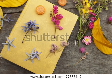 Closed yellow book with flowers and leaves still life on wood table background top view horizontal - stock photo