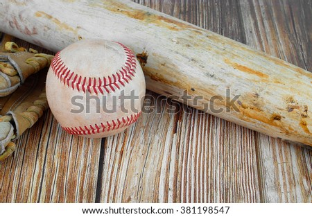 Closely cropped image of old, worn baseball equipment on a wooden background including a bat, mitt and ball Copy space in horizontal image. Concept of spring training, summer or fall playoffs. - stock photo