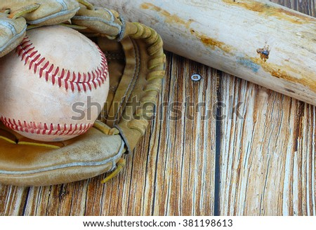 Closely cropped image of old, worn baseball equipment on a wooden background including a bat, mitt and ball. Great concept of baseball season including spring training or fall playoffs. - stock photo