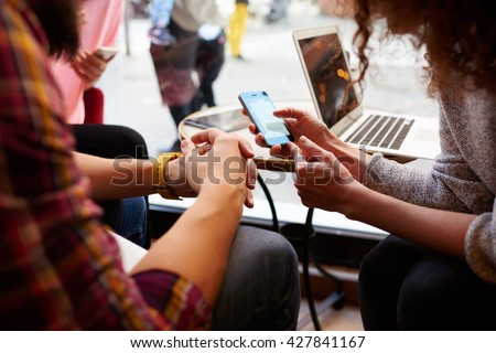 Closely image of woman is making an on-line purchase via cell telephone, while is sitting with friends in hipster cafe interior. Young female is reading information on web page via her mobile phone - stock photo