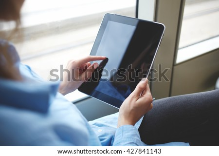 Closely image of woman`s finger is touching touch pad screen with copy space for your advertising text message or promotional content. Close up of hipster girl is downloading file on digital tablet - stock photo