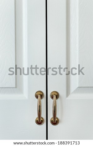 Closet wardrobe cupboard painted white with vintage handles hotel room - stock photo