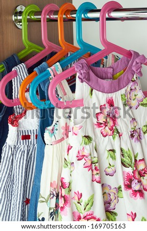 Closet with baby dresses on hangers  - stock photo
