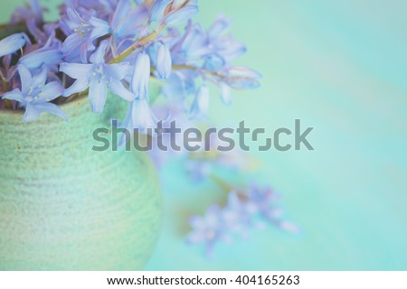 Closeup Aerial of Dreamy Pastel Lavender Lilly Flowers Spilling out of a Green Stoneware Vase with a Teal Blue Horizontal Wood Background with room or space for copy, text, your words to the side - stock photo