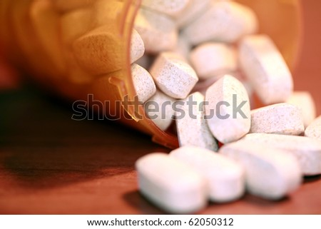 closeup aka macro shot of white pills spilling out of a orange plastic pill bottle on a table. This powerful image can represent, medication, over dose, drug abuse, addiction, medical help, and more - stock photo