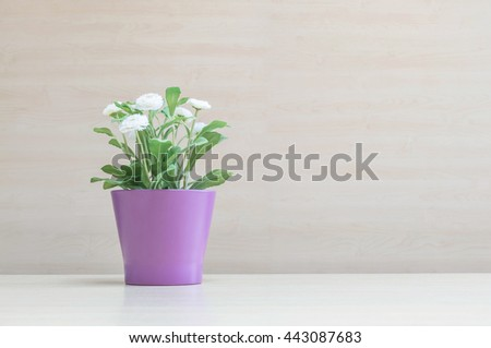 Closeup artificial plant with white flower on purple pot on blurred wooden desk and wall textured background in the meeting room under window light - stock photo