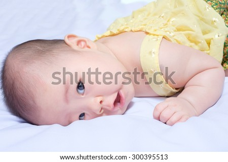 closeup asian baby girl in traditional thai dress, she lie prone, smile , open her mouth and looking at camera - stock photo
