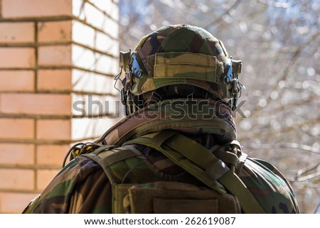 Closeup back view of soldier wearing camouflage helmet with headset radio looking outside  - stock photo