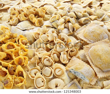 Closeup background of an assortment of handmade pasta with in a variety of shapes and fillings for Italian and Mediterranean cuisine - stock photo