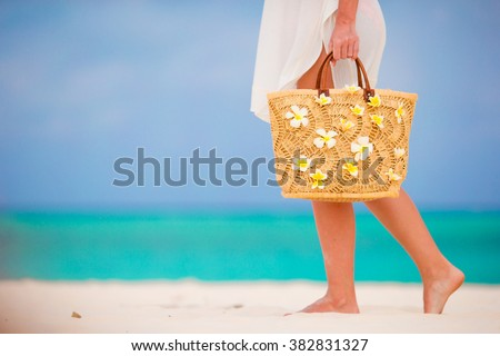 Closeup beautiful bag with frangipani flowers and sunglasses on white beach in female hands - stock photo