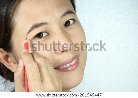closeup beautiful young woman with eyebrow brush added to eyebrows - stock photo