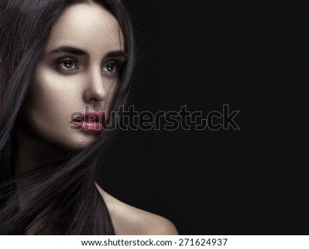 Closeup beauty portrait of a young beautiful brunette girl with long black straight flying hair. Magnificent hair. Looking away. - stock photo