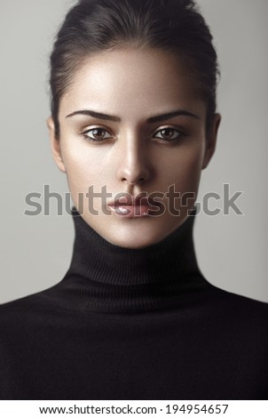 Closeup beauty portrait of a young brunette model in a black roll neck jumper. Be strong. - stock photo
