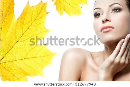 closeup beauty portrait of attractive caucasian young woman brunette isolated on white studio shot lips face head and shoulders yellow maple leaf autumn - stock photo