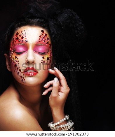 Closeup beauty portrait of attractive model face with bright rhinestones visage.Woman with eye closed. - stock photo