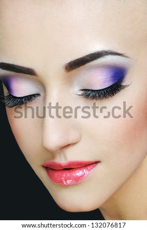 Closeup beauty portrait of attractive model face with bright visage. Multicolored eye makeup and pink lips make-up - stock photo