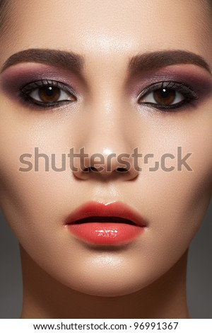 Closeup beauty portrait of attractive model face with bright visage. Purple eye makeup and gloss lips make-up - stock photo