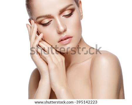 Closeup beauty portrait of attractive model with professional makeup. Blue eyes, brunette hair. Fresh, clean skin. Tender colors. Gold hands. White background, isolated. - stock photo