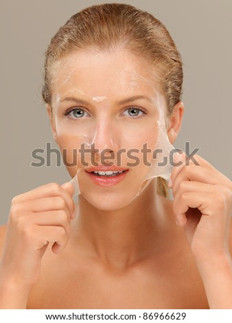 closeup beauty portrait of beautiful blonde woman peeling off a facial mask, smiling - stock photo