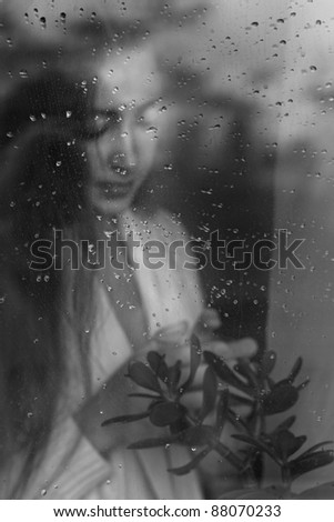 closeup beauty portrait of blonde woman blowing from behind a wet window - stock photo