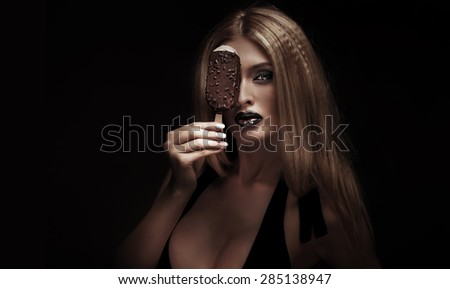 Closeup beauty portrait of sexy blonde woman with perfect fashionable makeup. Girl posing with chocolate ice cream. - stock photo