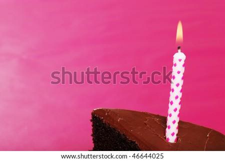 closeup birthday candle in slice of chocolate cake - stock photo