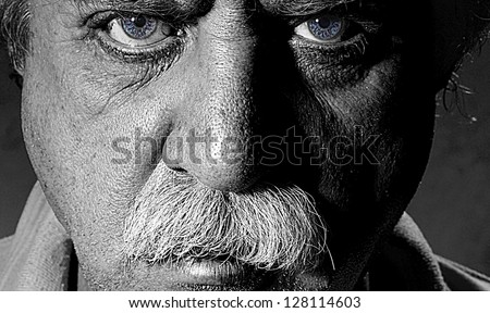 Closeup black and white character portrait of a man with blue eyes looking at the camera with questioning and suspicious facial expression - stock photo