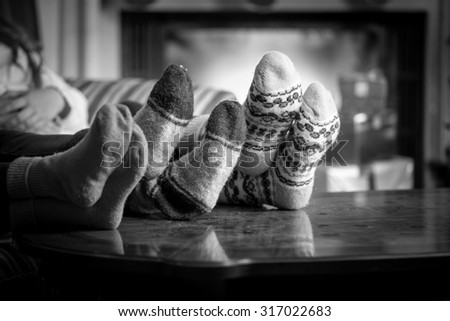 Closeup black and white photo family wearing woolen socks warming at fireplace - stock photo