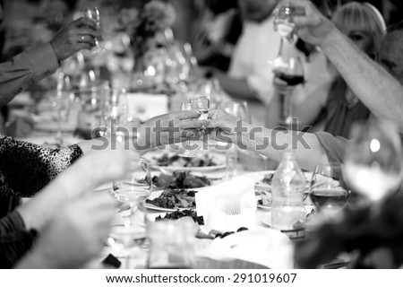 Closeup black and white photo of celebrating people clinking glasses with alcohol - stock photo