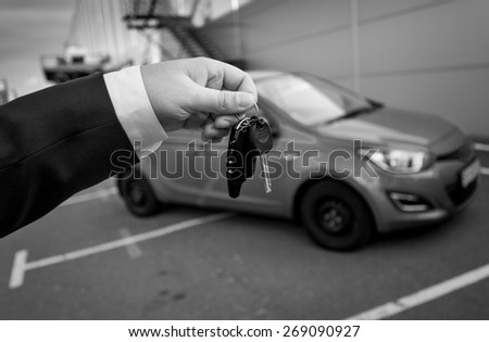 Closeup black and white photo of man in suit holding car keys against new car - stock photo