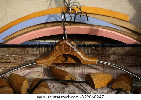 Closeup boot trees and varnish retro wooden coat hanger against lots of vintage clothing hangers angular frames made of timber  painted coloured tired aged background, horizontal picture - stock photo