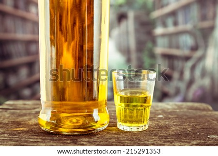 Closeup Bottle and one glass shot with yellow liqour resembling whiskey, rum, tequila, spirit on wooden table - stock photo